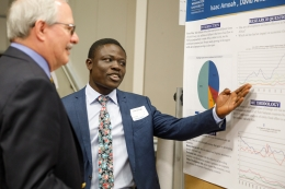 GW President Thomas LeBlanc and a GW student discuss the student's research poster