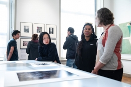 Students in an art gallery discussing some artwork