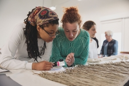 Students examining textiles together