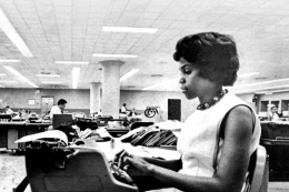 Dorothy Butler Gilliam sits at a desk with a typewriter in black and white photo of a newsroom