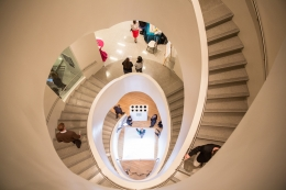 People walking on a white spiral staircase at the GW Textile Museum.