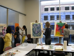 Students standing and painting in the classroom.