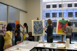Art Therapy students painting in a classroom.