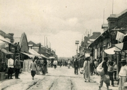 Black and white photo of people walking in a market street in what appears to be an east Asian town