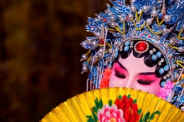 A female Beijing Opera performer with fancy headdress hides her face behind a painted fan.