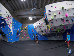 People in an indoor rock climbing gym, someone climbing on the wall