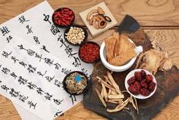 Bowls of Chinese traditional medicinal herbs sit on a table.