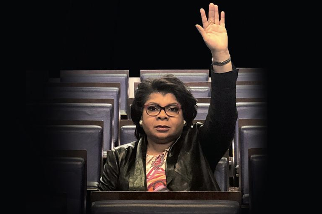 April Ryan with hand raised in the White House briefing room