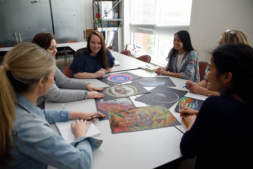 Art Therapy students sitting around a table discussing their artwork.