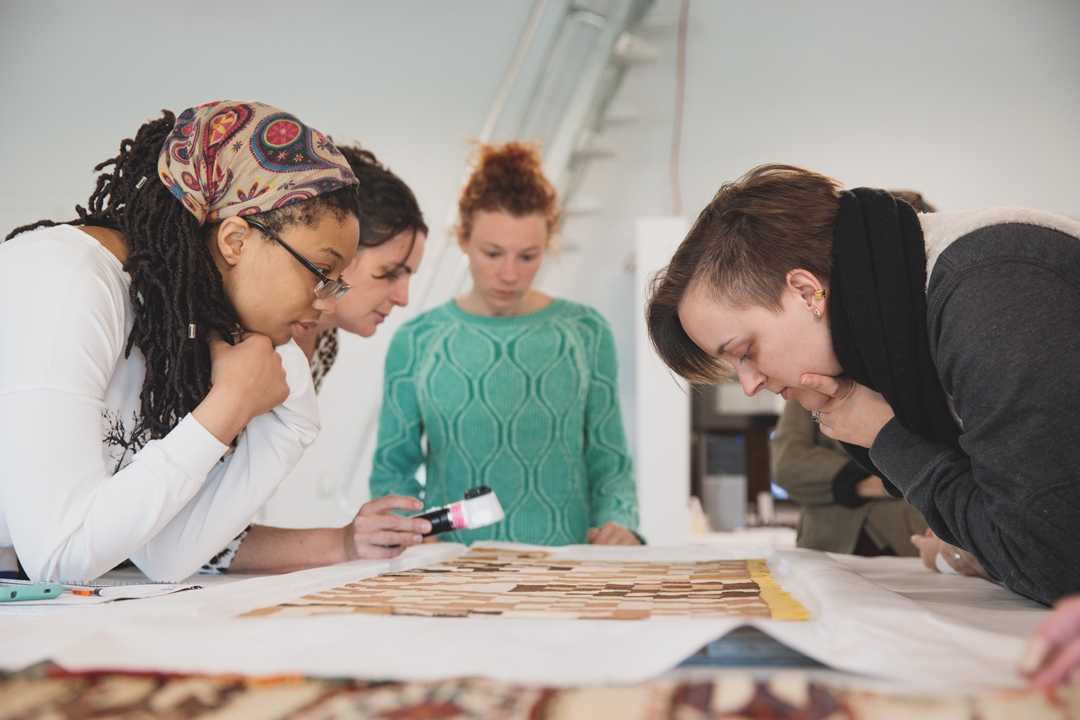 Decorative Arts and Design students look at textiles on a table in a classroom.