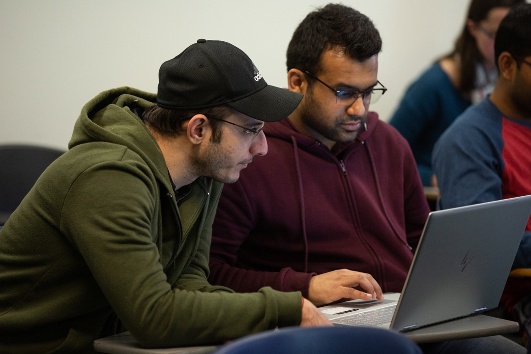 Two Data Science students working together on a laptop in class