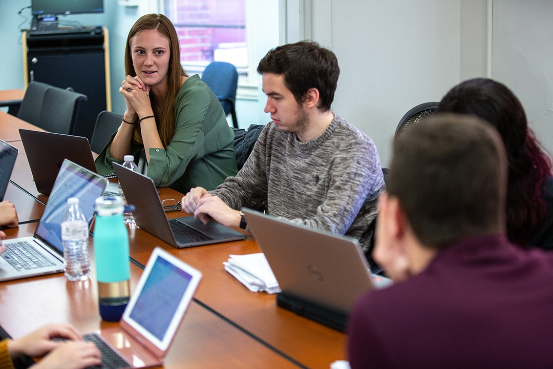 A group of students sitting along a long table in an Organizational Sciences class