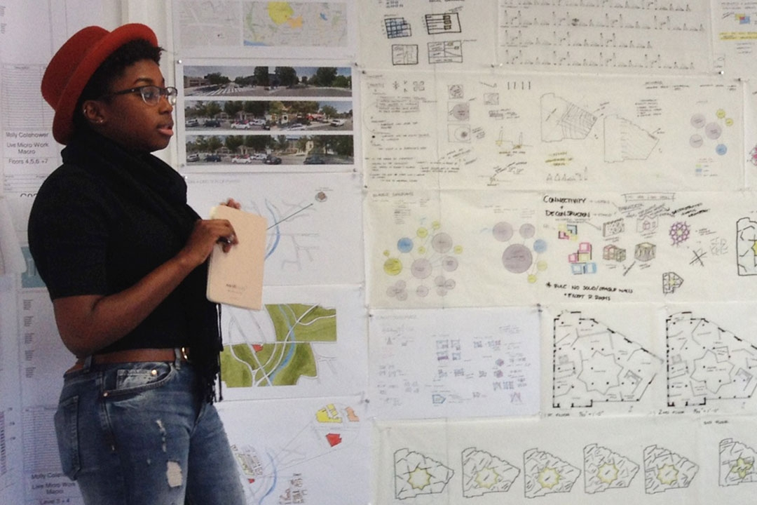 Student presenting in front of a wall covered in architectural drawings