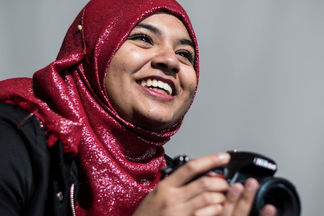 Smiling student holding a camera
