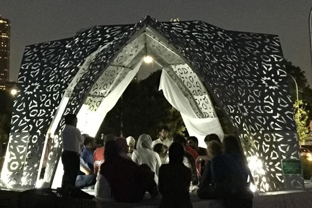 A group of people gather at an outdoor art installation at night.