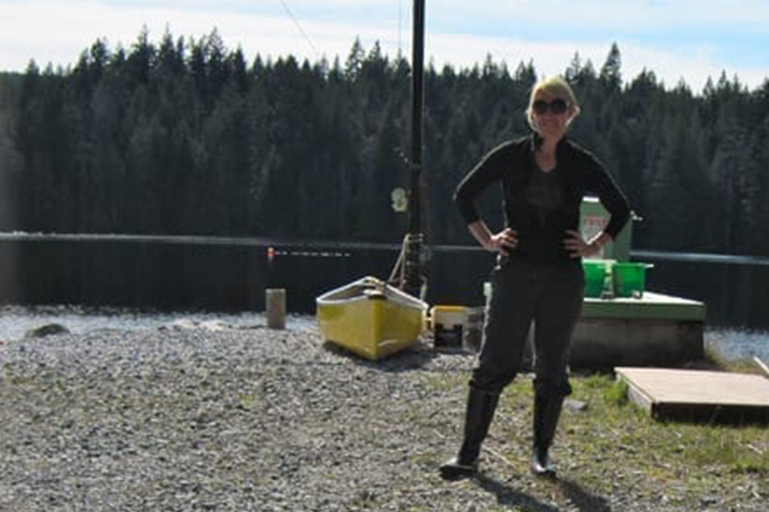 Dr. Robin Tinghitella stands near a lake and kayak