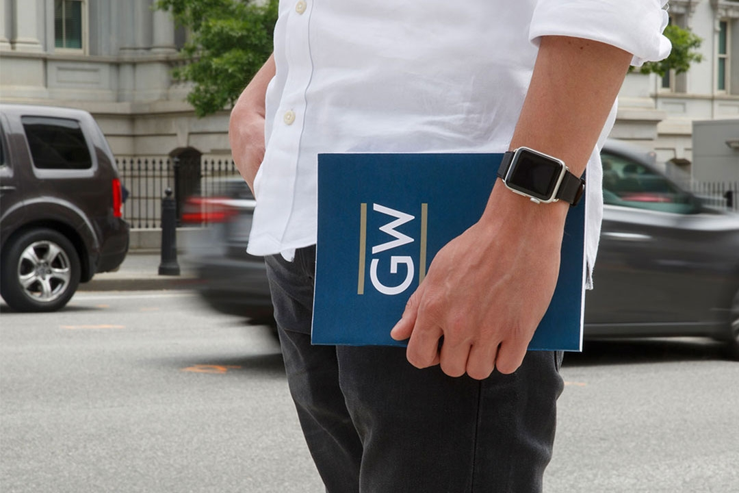 Student standing on a street in Washington, D.C., holding a GW folder.