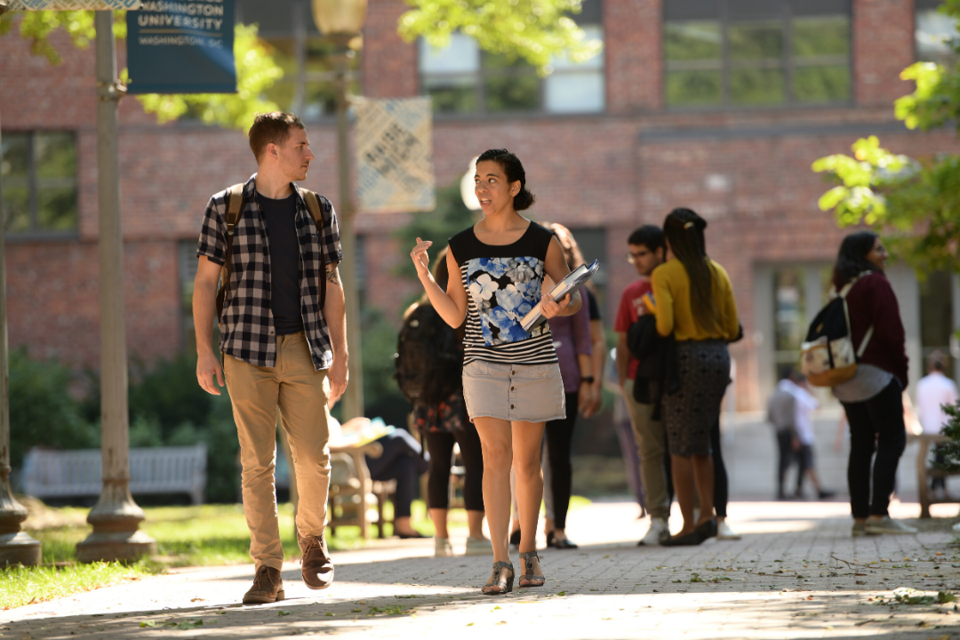 two students walk through the quad