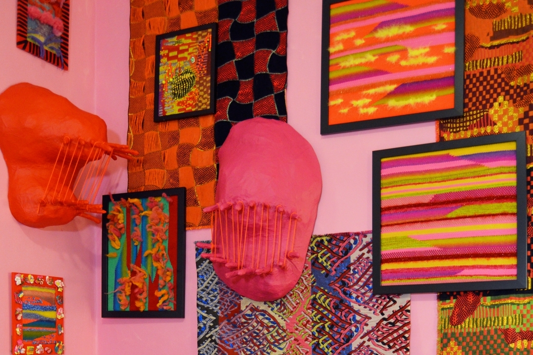 Pink and orange sculptures, framed artwork hanging on pink wall
