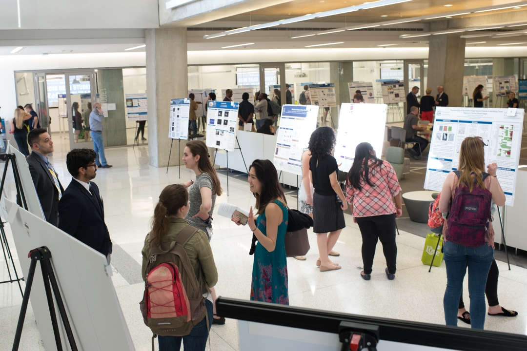 Students and visitors view research posters